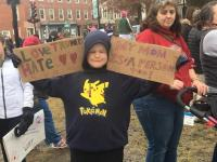 Liam holding his sign (right hand) and Kian's sign (left hand). Thanks to Sara Lowe-Bouchard for the photo. No, that's not my wife in the background.